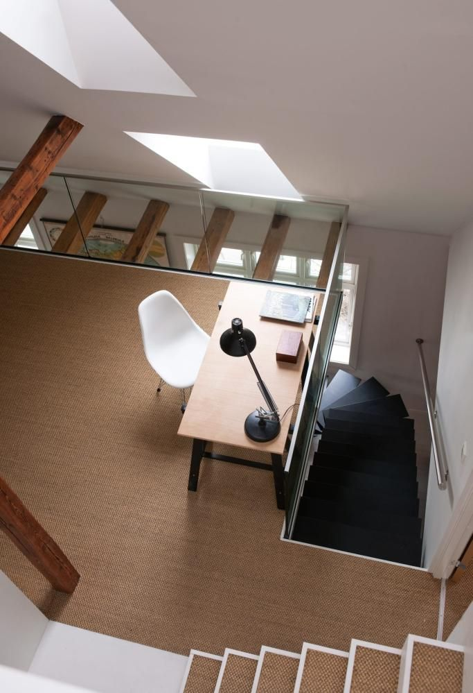 KONTAKT MELLOM ETASJENE: Et rekkverk av glass sørger for å ivareta kontakten mellom etasjene uten at det går på bekostning av sikkerheten. På gulvet er det lagt et vegg-til-vegg-teppe av sisal.
