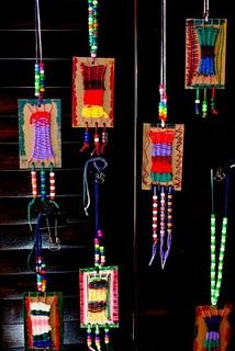 Mini weavings remain on their cardboard looms, decorated, and then turned in to a wearable works of art.
