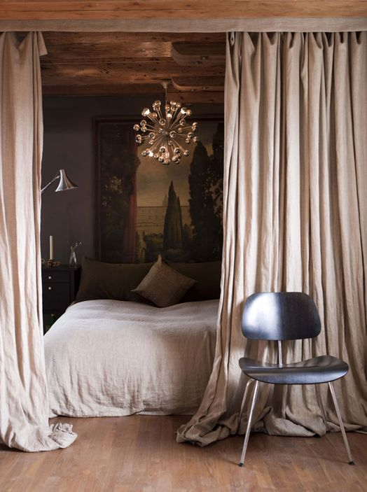 Curtains that pool on the floor and a retro light make a glamorous bedroom