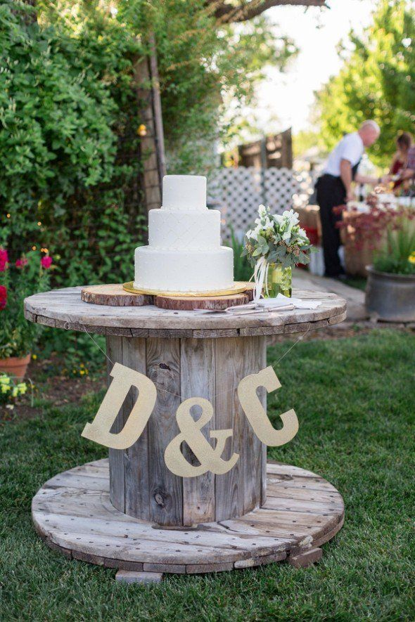 Letters hanging from wedding cake stand with gold glitter tablecloth underneath