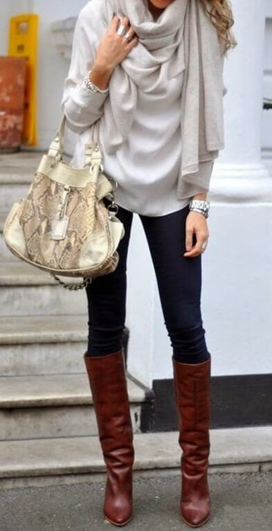 Woman on the sidewalk wearing a pale silver sweater, beige scarf, blue jeans and brown boots with a snakeskin handbag
