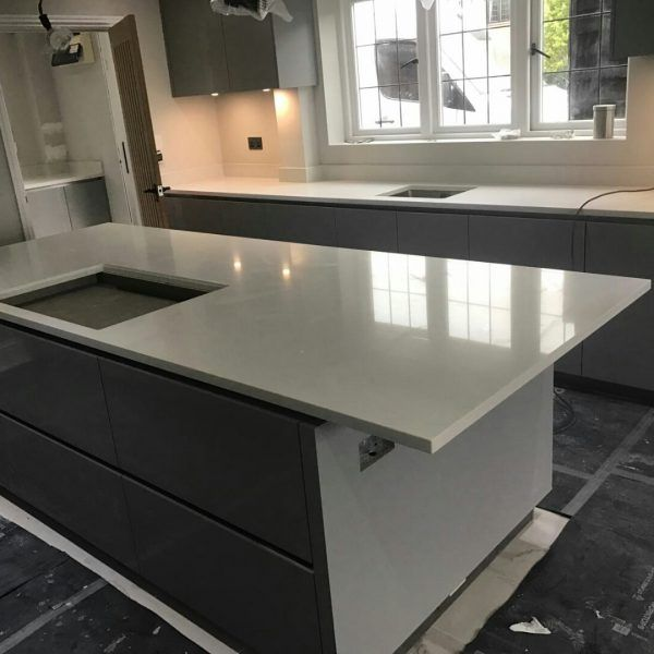 A large kitchen island with a breakfast bar situated on the end. A perfect piece in the kitchen that is topped off with the Bianco Carrina.