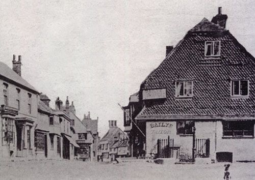 A view of Middle Row, East Grinstead, photographed by William Harding in 1864. The building on the right belonged to George Bailye, a tailor and hairdresser who resided in East Grinstead's High Street. The town well and pump, enclosed by railings, can be seen in front of Bailye's tailor shop. William Harding was managing a tobacconist's shop in Middle Row in the early 1860s around the time he took up photography. East Grinstead Photographers