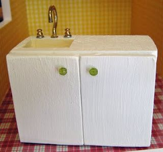 OMGOSH!! How cute - the faucet and knobs are made of a screw hook and two ear ring backs!! How inventive! (homemade dollhouse kitchen sink and cupboard)