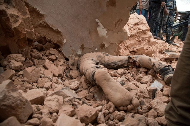 A victim of Nepal's earthquake lies in the debris of the Dharara tower after it collapsed on April 25, 2015 in Kathmandu, Nepal. More than 100 people have died as tremors hit Nepal after an earthquake measuring 7.9 on the Richter scale caused buildings to collapse and avalanches to be triggered in the Himalayas.