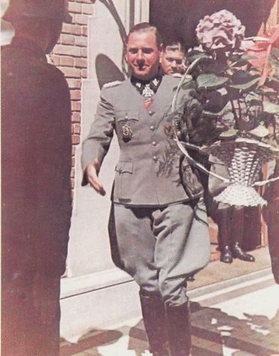 """Brigadefuhrer Fritz Witt carrying a floral tribute. This is from a series of colour photographs taken at the party given by the officers of his """"Hitlerjugend"""" Division to mark his 36th birthday, 25 May, 1944. On 14 June, 1944, Witt suffered the unusual distinction (for a Waffen-SS general) of being killed when his divisional headquarters at Venoix, Normandy, was hit by a British naval barrage. Best regards, JR."""