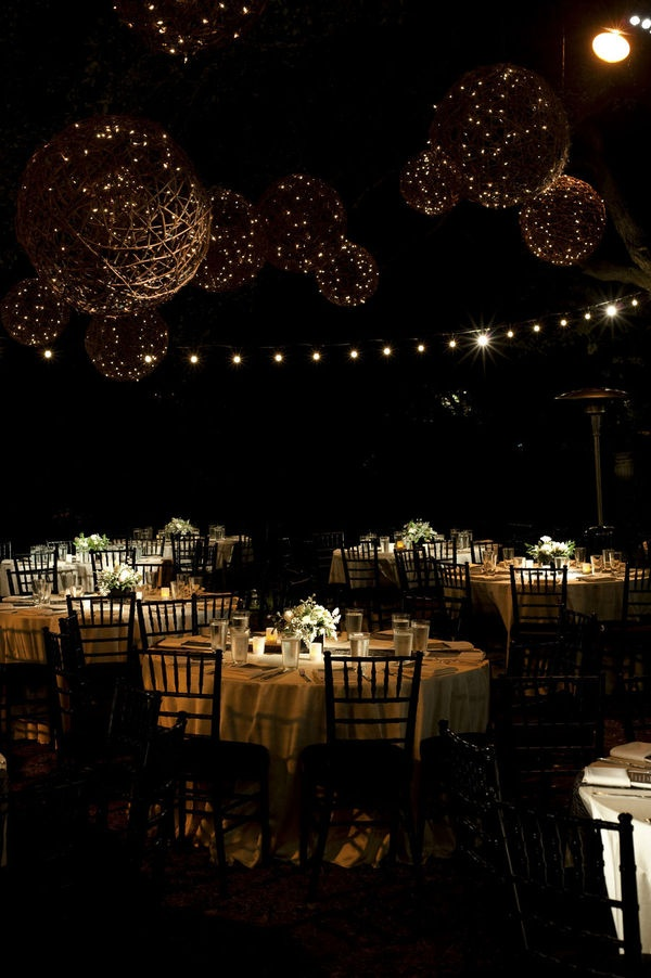 Gorgeous outdoor reception. Hanging twig spheres filled with twinkle lights.  Black ballroom chairs & gold table clothes.
