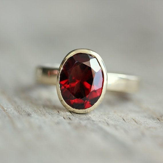 Oval garnet is bezel set in a handmade 14k Yellow Gold setting. Custom made to order. $610