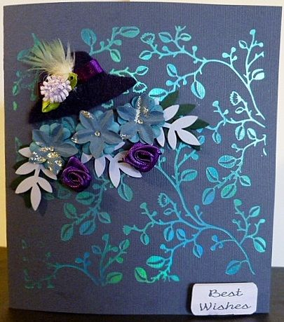 Made by Susan Powell-Barton - My first attempt at hot foiling with my Todo. Used blue card from my kit and the blue foil for the background. Made up a felt hat and popped a small flower with a budgie feather attached over purple ribbon. The flowers and leaves are punchies with a tad touch of glitter and small gems and two purple roses. Was very proud of myself and had a deal of fun.