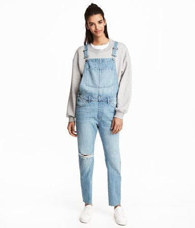 Light denim blue. Bib overalls in washed denim with heavily distressed details. Adjustable suspenders, buttons at sides, and tapered legs. Bib pocket, side