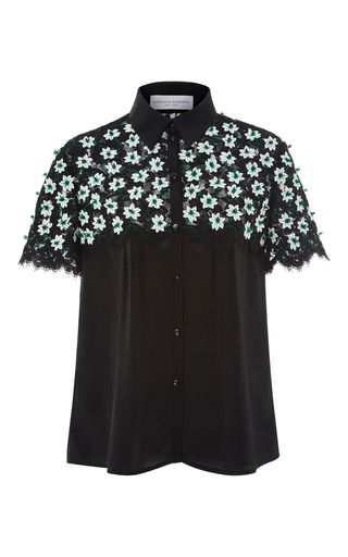 This short sleeve **Carolina Herrera** top features a button up style with a pointed collar, lasercut flowers detailing along the yoke and a slim fit.