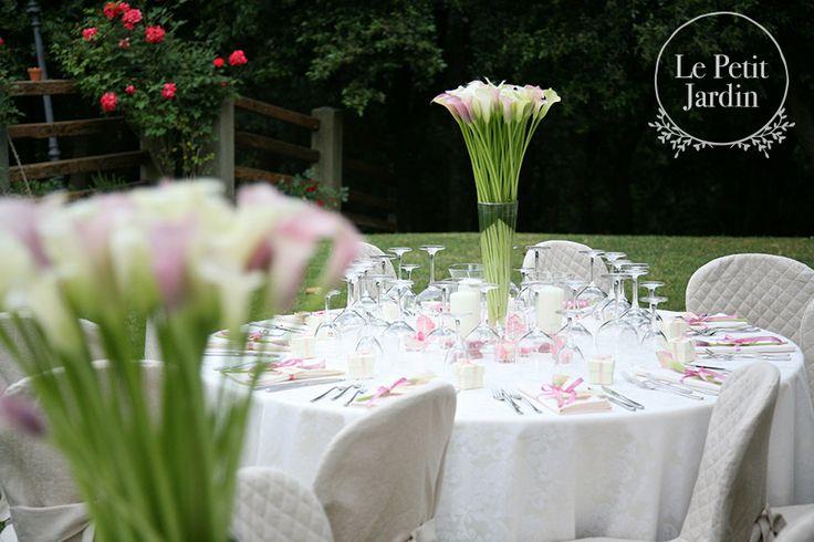 Splendidi vasi alti decorati con calle. Grandi candele alla base per dare un'atmosfera romantica e illuminare la tavola durante la notte.