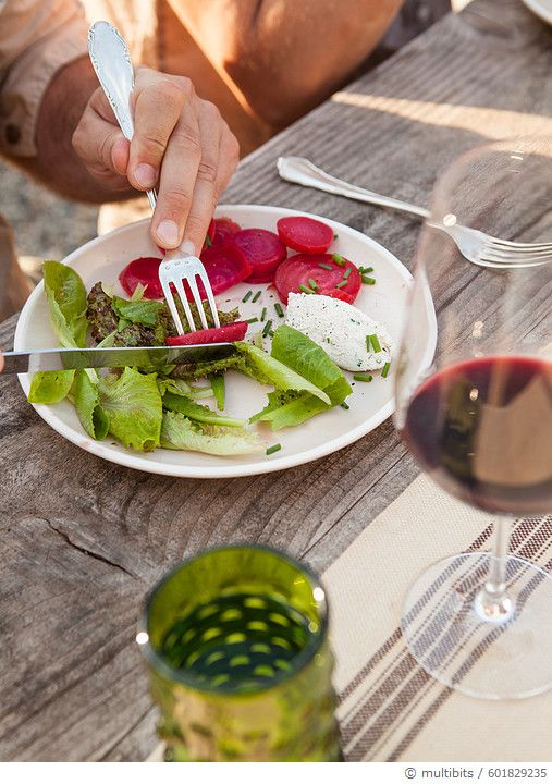Man cutting beets on salad plate w/wine - gettyimageskorea