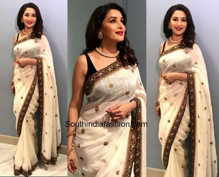 Madhuri Dixit in Nirjara   Madhuri Dixit was snapped wearing a white saree embellished with copper brown gold buttis and border. She paired up the Nirjara saree with a sleeveless black blouse. She further elevated her saree look with Curio Cottage Jewelry.  Her beauty look included bold red lips and loose wavy hair-do. She looked nice!  Related Posts  Madhuri Dixit in Abu Jani and Sandeep Khosla  Madhuri Dixit in Anita Dongre  Madhuri Dixit in Manish Malhotra  The post Madhuri Dixit in…