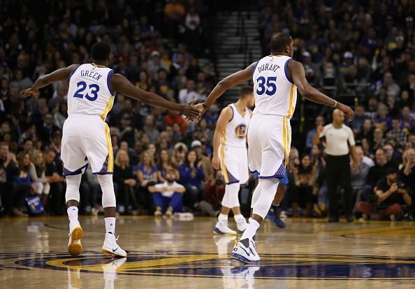 Draymond Green of the Golden State Warriors highfives Kevin Durant during their game against the Dallas Mavericks at ORACLE Arena on December 30 2016...