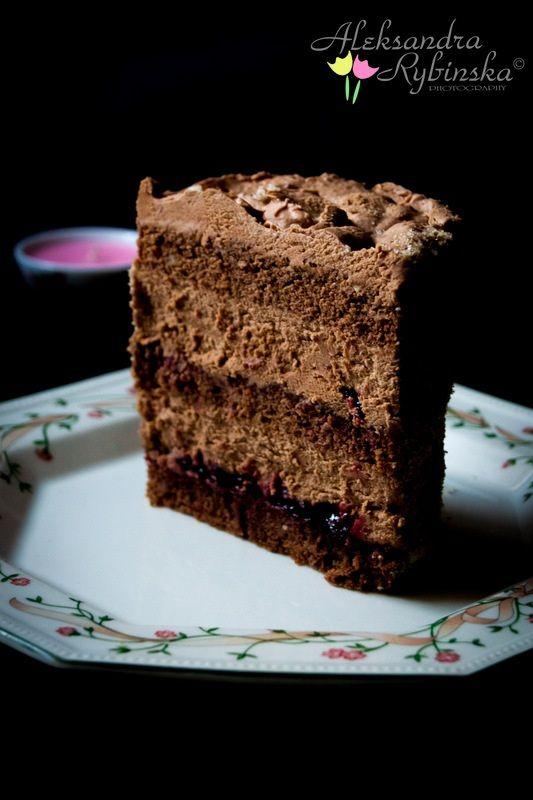 Tort składa się z biszkoptu czekoladowego z orzechami laskowymi, z masy pralinowej i dżemu porzeczkowego.