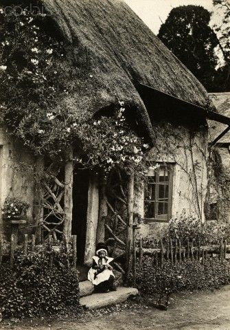In rural England, a child sits outside an old English cottage.