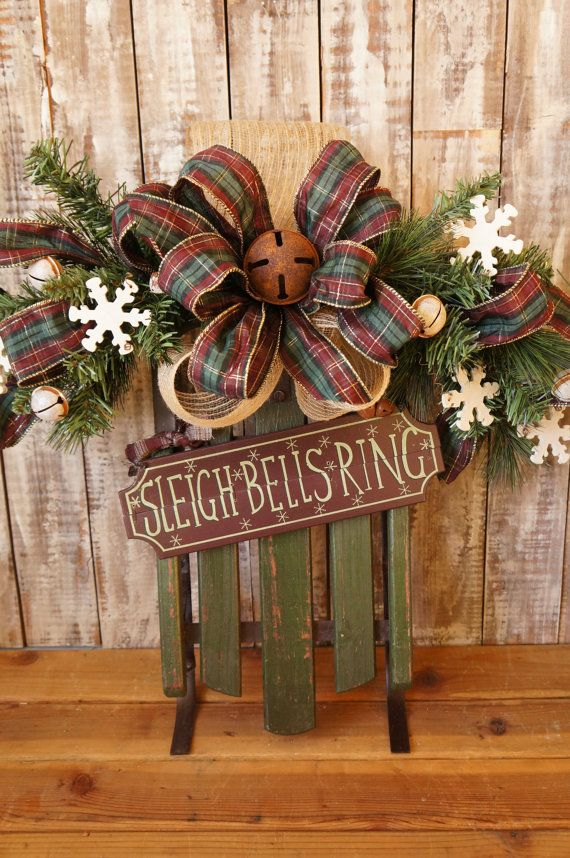 A charming old fashioned touch to your Christmas decorating. This rustic sled / sleigh Christmas door hanger / wreath, is a perfect way to welcome guests to your front door or to use anywhere as a decorating accent. Complete with a real decorative sled with metal runners, sleigh bells, wooden snowflakes, an old fashioned rustic plaid ribbon, deco mesh burlap and a pine swag. Approximately 26 inches long. ***MORE CHRISTMAS HERE…