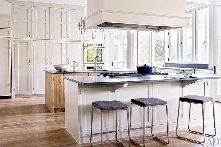The kitchen is equipped with a Thermador cooktop and ovens; the barstools are by Room & Board.