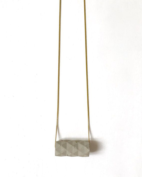 The concrete origami cylinder is casted around a raw brass cylinder. Original geometric form, this necklace will add a twist to your wardrobe.