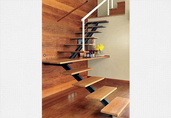 Para aproveitar o vão sob a escada, a arquiteta Cristina Bozian estendeu à direita a prancha que compõe o patamar e vai até a parede, também de madeira. Ali, funciona um charmoso bar