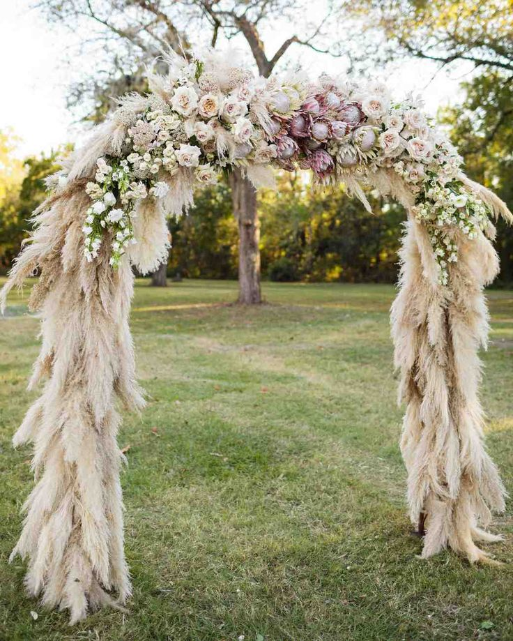"""""""We were trying to keep it bohemian and natural but greenery doesn't really pop in an outdoor ceremony in a green field with green trees in the background,"""" planner and designer Julie Savage Parekh of Strawberry Milk Events says of the ceremony arch. So pampas grass covered the structure, which was topped with groupings of flowers.   Photography: Koby Brown"""