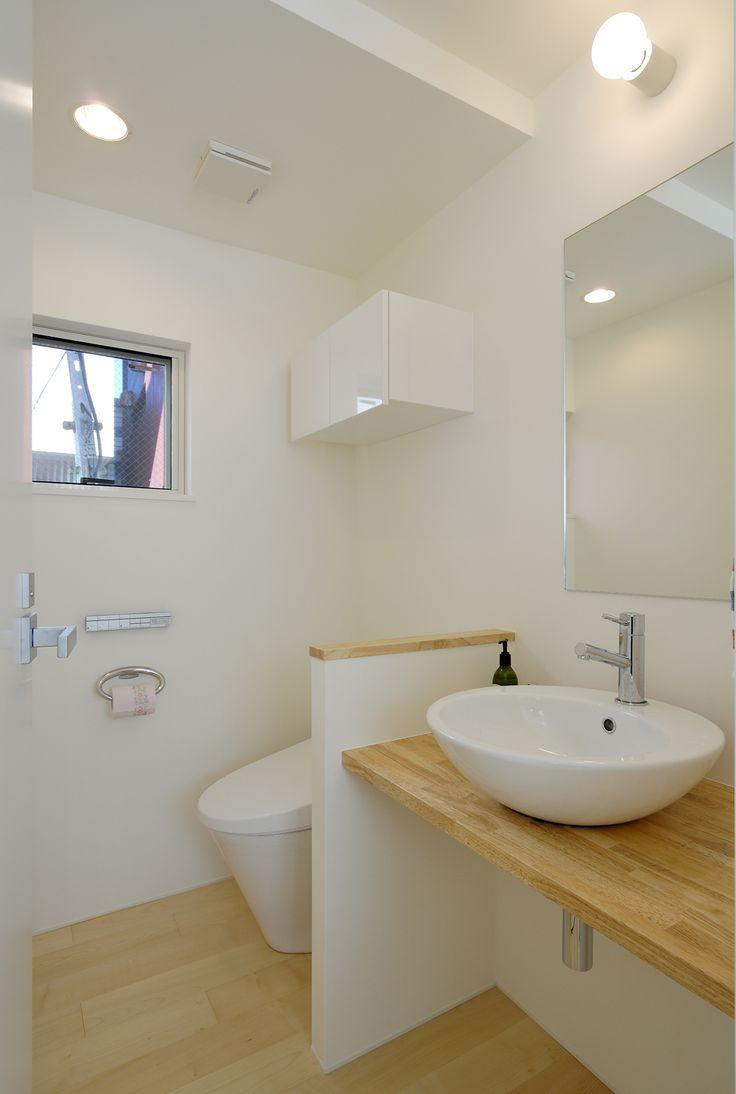 白木と白を基調にした、トイレと洗面所をユニットさせ広さを強調した空間