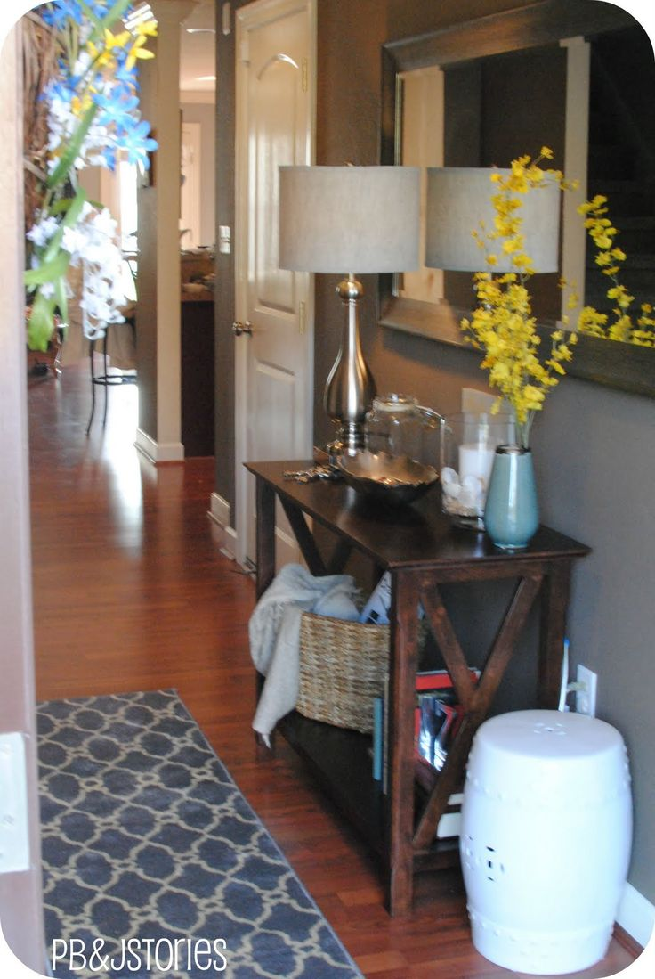 Entryway console rug lamp flowers stool on the side Foyer console decorating ideas