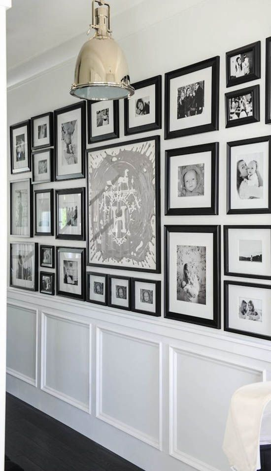 Black framed family photographs in a modular layout in the family home of Monica Hibbs.