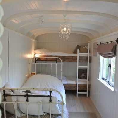 RV Bus conversion.  Love the white, wood, and iron bed.  Also the chandelier.  Gorgeous, simple.