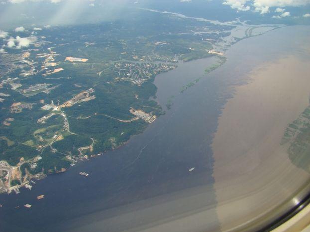 Vista aérea do encontro das águas dos rios Negro (águas escuras) e Solimões (águas barrentas), resultando no rio Amazonas. As águas não se misturam por quilômetros. Há diferença na temperatura das águas inclusive. Estado do Amazonas, Brasil.  Fotografia: glaubercr no http://www.mochileiros.com