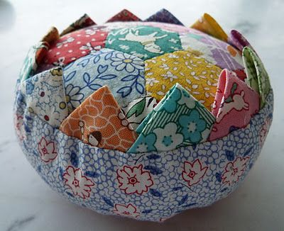 Prairie Points Pin cushion.. Pattern here , but I like the round bottom better http://www.unitednotions.com/fp_prairie-flower-pincushion.pdf