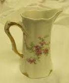 Pieni ja sievä kermanekka/kannu, kukka- tai muulla sievällä kuvalla (nalle tms.), mahdollisesti kultareunuksella, myös erikoisemman mallinen, posliinia tai lasia