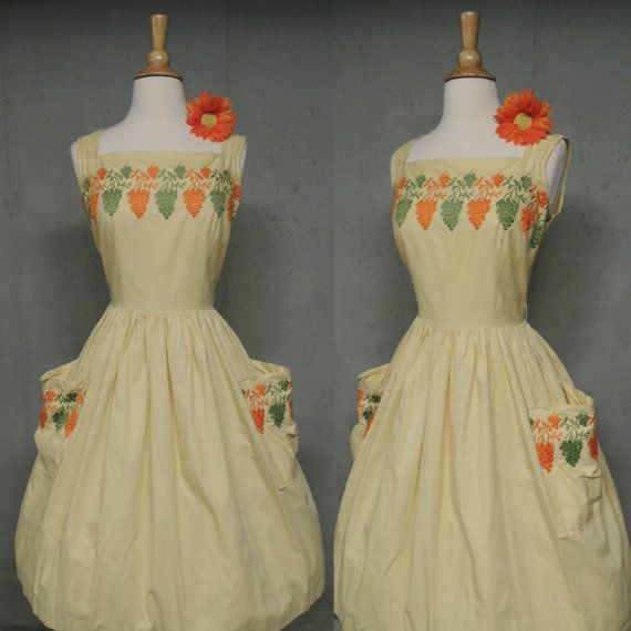 Darling cotton frock. Novelty embroidered grapes. Butter yellow with tangerine and lime green needlework. Fitted bodice. Nipped waist. Full skirt with patch pockets. Back metal zipper. Bust 34 Bodice 15 1/2 Waist 26 Hips free Length 40 Good condition. Has a couple of areas of spots.