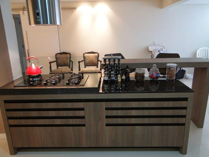 Armários de cozinha em MDF com melamínico de madeira escura com puxadores de alumínio pintados. Tampo em granito marrom imperial e cooktop. Muito charmosa esta combinação na cozinha.