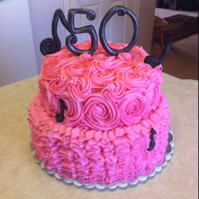 50th birthday cake for a music lover! Two tier (10 in 8 in) chocolate fudge and vanilla with vanilla buttercream. Ruffle frosting on bottom tier and roses on top tier. Music notes and 50 are fondant.
