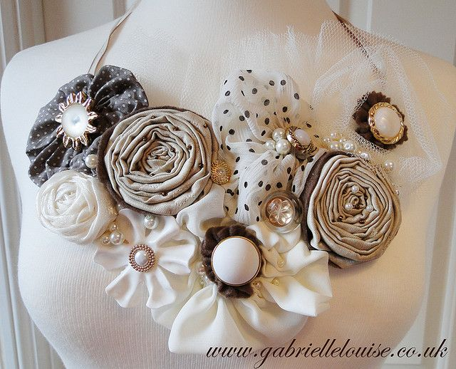 www.gabriellelouise.co.uk  Elizabeth is a beautiful fabric flower necklace made using a mixture of vintage fabrics, quality bridal fabrics, and net, and decorated using vintage buttons and pearl beads.   The necklace can be worn as a necklace or a statement choker as it fastens with a long ribbon so the wearer can decide where the necklace hangs.   The colours are browns, cappuccino, ivory and gold, the perfect accessories for any bride, bridesmaid or party goer wanting to make a statement
