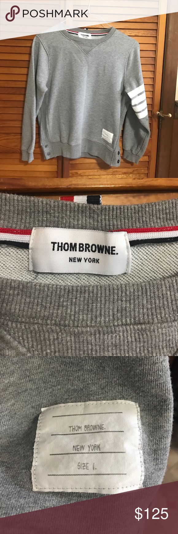 Thom Browne gray pullover sweatshirt size 1 Women's Thom Browne pull over sweatshirt size 1 (XS-S). Sweater is light gray in color with 2 striped sleeve. Sweater is in great used condition but does have a few faint light spots that almost blend into the sweater (almost like a detergent grease stain). No rips/holes. Thom Browne Sweaters Crew & Scoop Necks