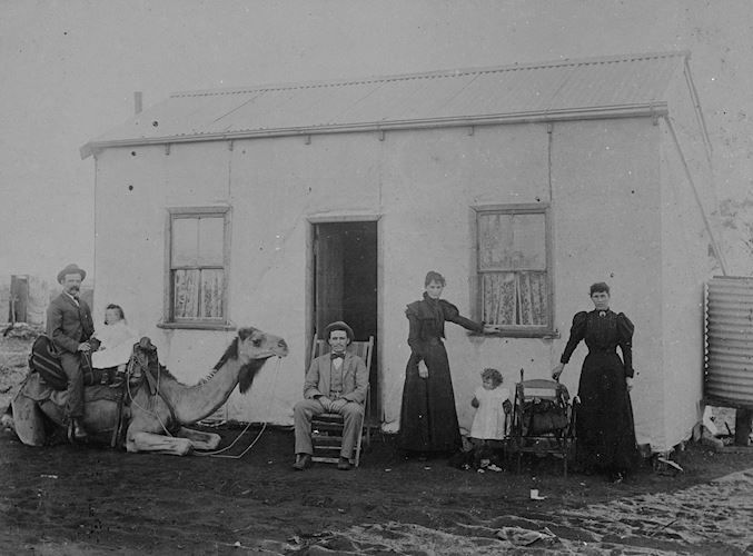A group of people in front of a small, plain house in the Coolgardie District of Western Australia. On the left a man and a toddler sit on a kneeling camel, a man sits on a deck chair in front of the entrance while two women and another small child stand on the right. There is a water tank on the far right. The image was created by the W Roy Miller Studio in circa 1900.