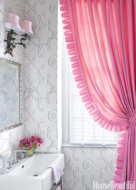 This Virginia townhouse is a study in pink, so a powder room's feminine curtain follows suit. Nina Campbell's geometric Ornella wallpaper tempers the cheery hue. Click through for more of the best bathroom colors and designs.