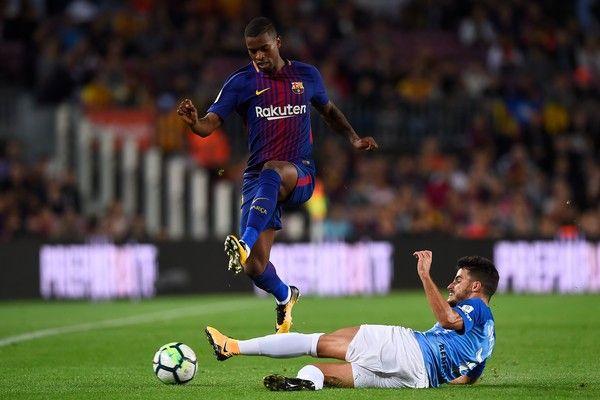 Barcelona's Portuguese defender Nelson Semedo challenges Malaga's defender Juan Carlos Perez (R) during the Spanish league football match FC Barcelona vs Malaga CF at the Camp Nou stadium in Barcelona on October 21, 2017. / AFP PHOTO / Josep LAGO