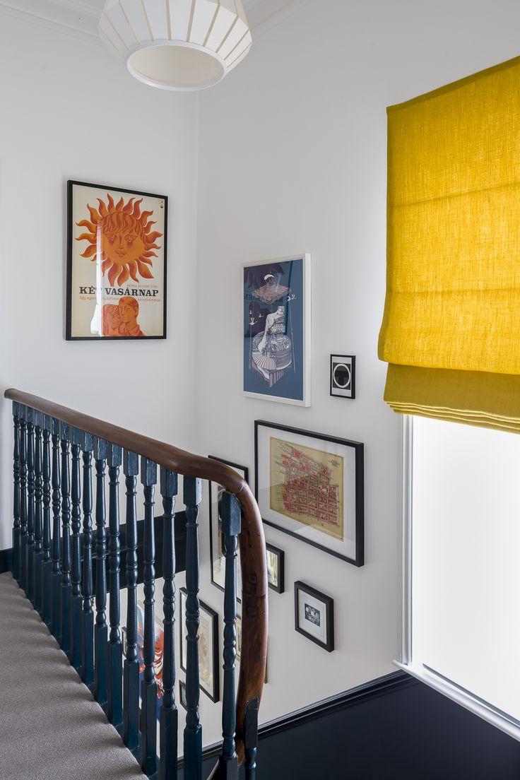 Interior Design von Imperfect Interiors in dieser viktorianischen Villa in London. Eine Palette zeitgenössischer Farben von Farrow & Ball, gemischt mit traditionellen Details aus der Zeit – Hague Blue-Spindeln und weiße Wände, ein sonnengelbes römisches Raffrollo aus Leinen und eine Galeriewand mit zeitgenössischen Drucken, die von der Eingangshalle die Treppe hinauf führen. Foto von Chris Snook