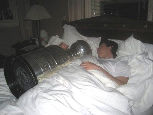 Pittsburgh Penguins Captain Sidney Crosby sleeping with the Stanley Cup after winning it in 2009. Love it.