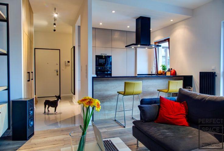 Aneks kuchenny połączony z salonem. Szafki kuchenne zabudowane pod sufit wraz ze sprzętem AGD oraz bar z hokerami nadają jej nowoczesnego charakteru.