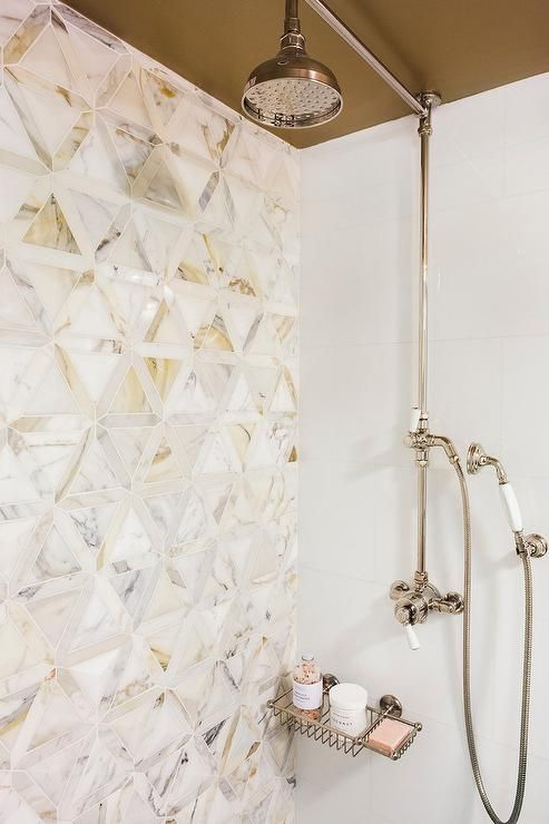 Stunning shower is fitted with a polished nickel exposed plumbing shower kit finished with a rain shower head mounted to a taupe ceiling complementing an accent wall covered in Artistic Tiles Duomo 3D Tiles.