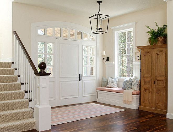 Family Home Interior IdeasThis foyer also features a built-in window seat bench with pink cushion and accents pillows. Notice the beautiful door, window trims, and the custom wainscoting.  Floors are site finished American Black Walnut.