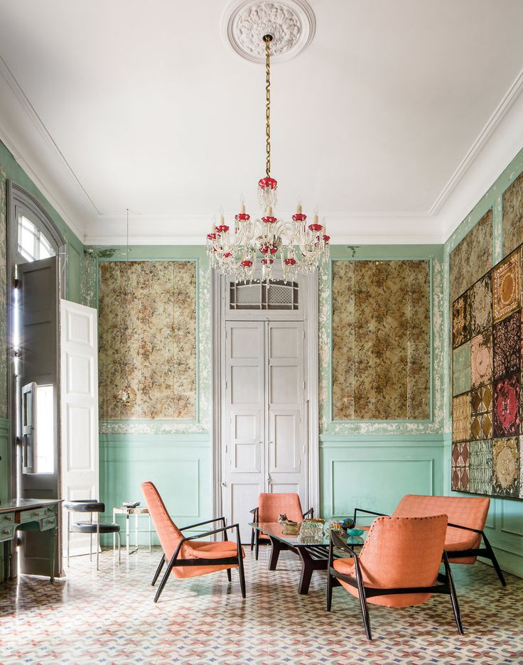 In the living room, midcentury furniture contrasts with wallpaper that predates the revolution. (Photo: Stefan Ruiz)