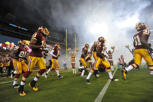 The Washington Redskins run onto the field before the NFL season opener against the Dallas Cowboys at FedExField on September 12, 2010 in Landover, Maryland.