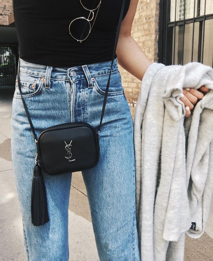 90's Style at best: high-waist jeans, black top, round sunglasses and ysl-crossbody
