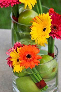 Außergewöhnliche und farbenfrohe Tischdeko mit Gerberas und grünen Äpfeln.